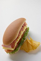 Ham, cheese, tomato and lettuce sandwich with crisps