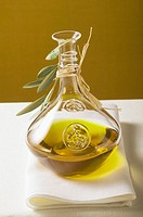Olive oil in carafe with olive branch