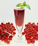 Cherry juice in glass with mint leaf, surrounded by cherries