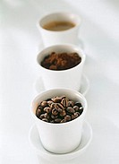 Coffee beans, coffee powder and espresso in bowls