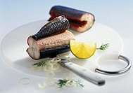 Smoked eel in pieces, garnished with lemon and onion