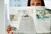 20 yr old woman reading newspaper at home