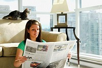 20 yr old young woman sitting in apartment reading newspaper