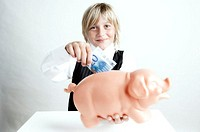 Portrait of a boy inserting money into a piggy bank