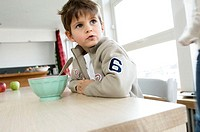 Boy sitting at the dining table with a bowl in front of him