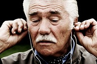 Close-up of a senior man listening to music on headphones
