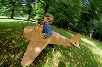 Side profile of a girl running with a model airplane