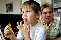 Close-up of a boy eating a chocolate bar with his father sitting behind him