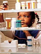 Child looking at medicines. Parents should keep all medicines out of reach of children.
