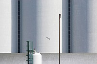 A seagull flies past storage tanks.
