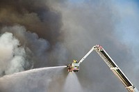 Firefighter in crane sprays water on fire through clouds of black smoke. Perth, Western Australia