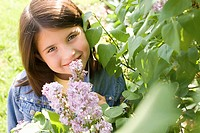 Girl smelling lilac blossoms