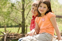 Boy and girl sitting on wooden fence