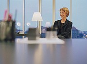 Young businesswoman sitting in office, smiling, dusk (focus on woman)