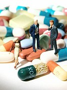 Miniature figures standing on pills