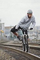 Young male cyclist balancing mountain bike on railway tracks
