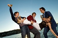 Three men holding woman on pier