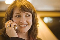 Young businesswoman using mobile phone, smiling, close-up