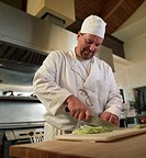 Mature male chef chopping celery in commercial kitchen, smiling