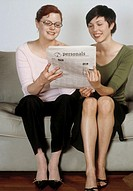 Two young women sitting on couch, reading personals