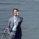Businessman standing next to bicycle, talking on mobile phone