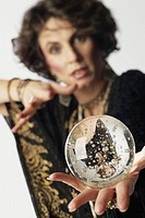 Woman holding out crystal ball, (focus on crystal ball) portrait
