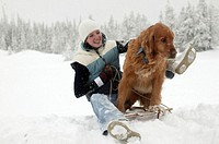 Young woman and golden retriever on sled in snow