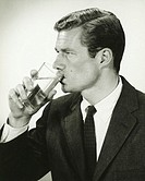 Young businessman drinking water, in studio, (B&W), portrait