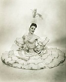 Woman in Latino dance costume sitting in studio, holding drum, (B&W)