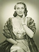 Fashionable woman in evening dress and mink stole posing in studio, (B&W), portrait