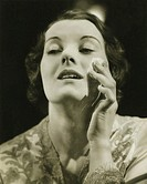 Woman removing make up in studio, (B&W), close-up