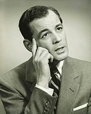 Businessman daydreaming in studio, head resting on hand, (B&W), close-up
