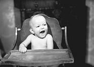 Baby (6-9 months) sitiing in high chair, (B&W)