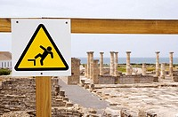 A sign on a wooden railing warns visitors to be aware of uneven surfaces, Baelo Claudia Archaeological Site, Andalucia, Spain