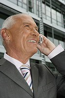 Manager talking on cell phone, office building in the background