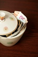 Sugar bowl filled with Euro bills (part of), close-up (thumbnail)