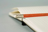 Pencil lying on an empty notebook, close-up, selective focus