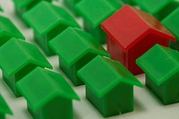 Red plastic miniature-house standing amongst green ones, selective focus