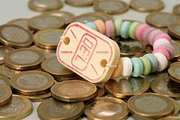 Wristwatch made of sweets lying on an accumulation of 1-Euro coins, close-up