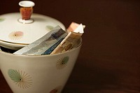 Sugar bowl filled with Euro bills (part of), close-up
