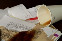 Overturned paper cup with coffee next to documents and a colored crayon