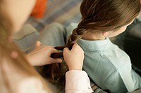 Girl plaiting friend's hair