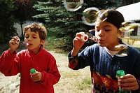 Girl and boy (7-9) blowing bubble-wands, outdoors