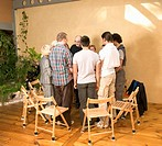 Group of people standing in circle in front of chairs