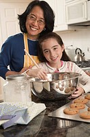 Grandmother and granddaughter baking cookies, portrait