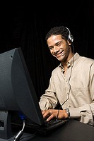 Man wearing headset and using computer