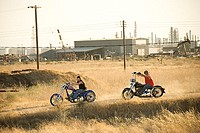 Men driving motorcycles on a dirt road