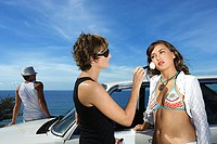 Woman having make-up applied in front of a car