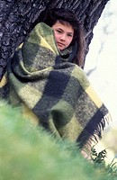 Girl wrapped in blanket, outdoors