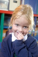 4 year old girl smiling into camera at nursery, with her hand up to her mouth